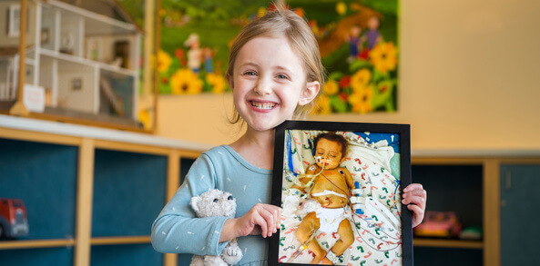 Image of 6-year-old Olivia, now healthy and smiling, holding a photograph of herself as a hospitalized and intubated infant